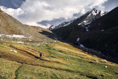 Small tourist with backpack is walking in the green mountain valley with snowy peaks and cloudy sky background 免版税图像