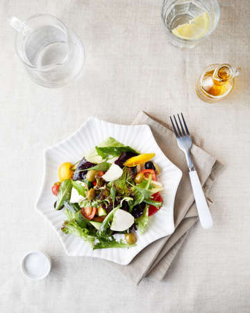 Vegetarian salad with fresh greenery, cucumbers, tomato and olives on the plate near water with lemon and olive oil bottle top view