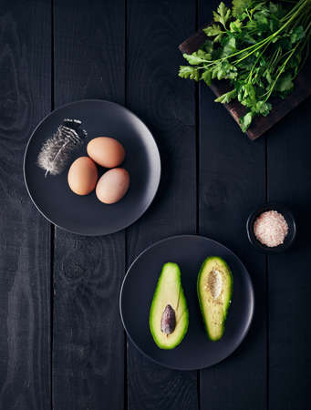 Boiled eggs, greenery and Avocado with Himalayan pink salt on dark wooden background