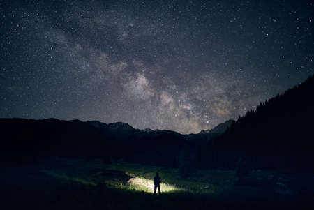 Silhouette of man is illuminating field with headlamp in the mountains under night sky with stars.