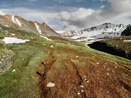 Two small tourists with backpack are walking in the green mountain valley with snowy peaks and cloudy sky background. Aerial view picture taken by drone.
