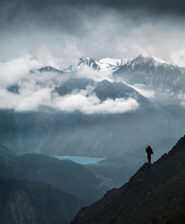Hiker in silhouette stands on the rock in the beautiful mountain scenery with lake and snowy summits