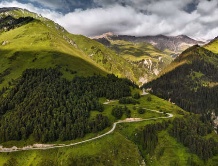 Aerial view of the road in the mountain valley with lush forest in Kazakhstan