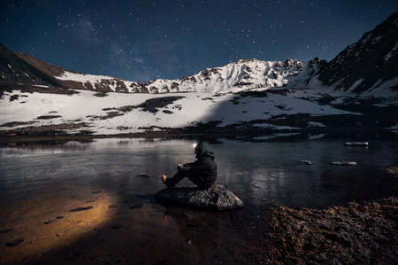 Man with his head light is looking at the lake at starry night the mountains