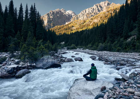 Young man doing yoga meditation in Padmasana sitting position on the rock near the river with mountain at sunrise at background.