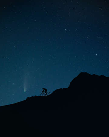 Silhouette of man riding the bicycle at the mountains under night sky with stars and Neowise comet.