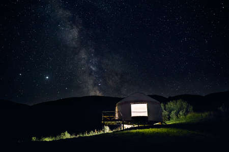 Beautiful gloving Yurt nomadic house at camping in the mountain valley under night sky with stars and Milky Way 免版税图像
