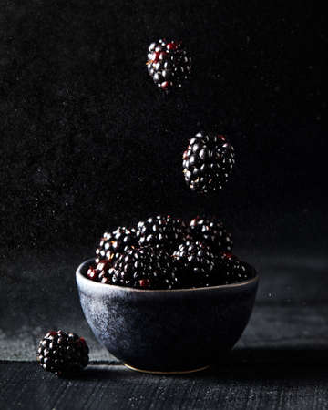 Fresh blackberry levitation on dark black background close up