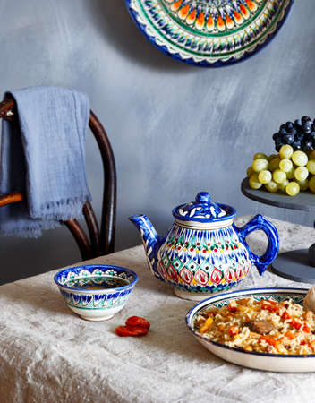 Uzbek traditional food pilaf, green tea and fruits in national dish during Nauryz festival at dark blue background