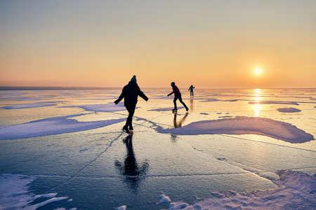 People are ice skating in silhouette at frozen lake against beautiful orange sunrise Zdjęcie Seryjne