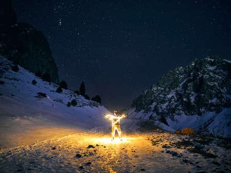 Man with Glowing orange garland in at winter mountains at dark night sky