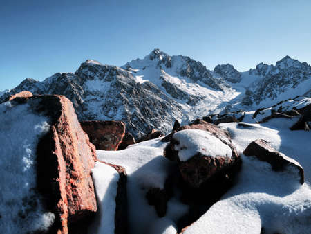 Sunny day at high mountains with snow against blue sky at winter time in Kazakhstan