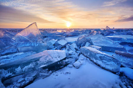 Beautiful landscape of Ice hummock with flare of sunset light at ice of lake Baikal, Russia