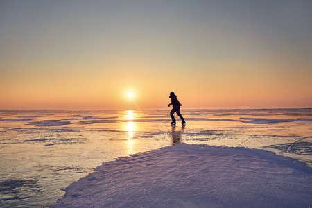 Man ice skating in silhouette at frozen lake against beautiful orange sunrise