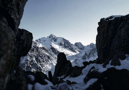 Beautiful panorama at high mountains with snow and black rocks against blue sky at winter time in Kazakhstan