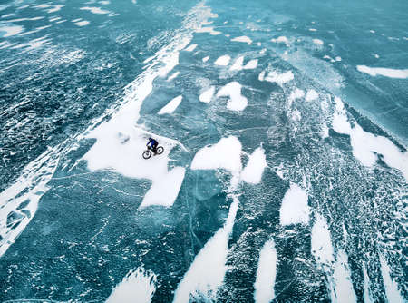 Top view drone shot of man at bicycle riding on the frozen lake with ice texture. Zdjęcie Seryjne