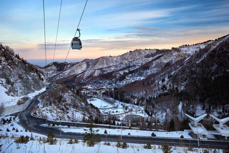 Cableway with funicular in the winter mountains at near Medeo Skate arena at sunrise in Almaty, Kazakhstan