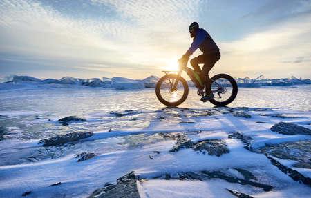 Man ride fat bike at frozen lake Kapchagay in Kazakhstan