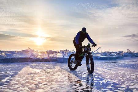 Man make turn at fat bike on the frozen lake Kapchagay at sunset in Kazakhstan Zdjęcie Seryjne