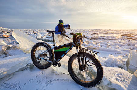 Man is have a tea brake near bicycle at frozen lake on sunset in Kazakhstan