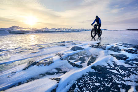Man ride fat bike at frozen lake Kapchagay on sunset in Kazakhstan