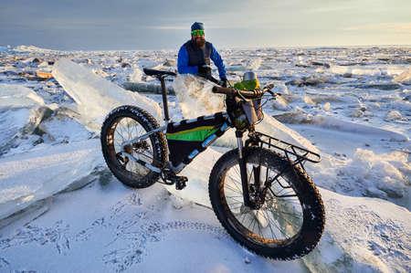 Man near bicycle at frozen lake on sunset in Kazakhstan