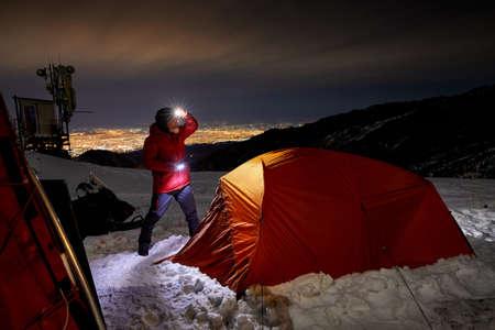 Old Climber with glowing headlamp near orange tent in the winter mountain ski resort Shymbulak at dark night sky in Almaty, Kazakhstan