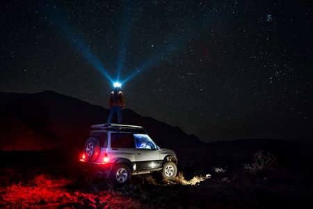 Woman with his head light is looking at the at starry night sky at off road car in the desert