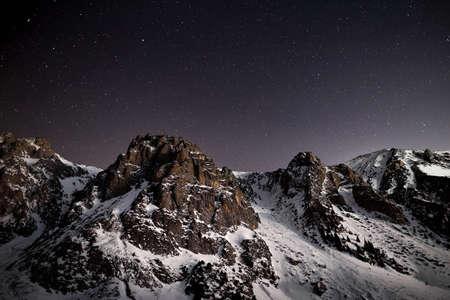 Dramatic landscape of mountain range at night sky with stars near Almaty, Kazakhstan