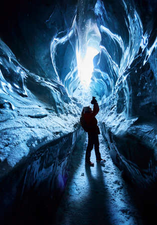 Silhouette of photographer with camera and backpack is taking pictures of amazing glacial ice cave in the mountains of Kazakhstan