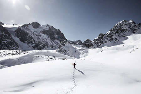 Man with backpack walking on the snow hill in the beautiful mountains against blue sky in Almaty, Kazakhstan Stock Photo