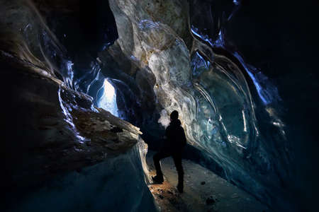 Silhouette of man exploring an amazing glacial ice cave in the mountains in Kazakhstan