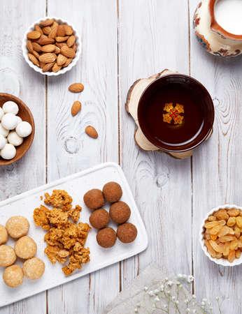 Kazakh national food like zhent, kurt, milk, sweet balls from cottage cheese, nuts and raisins during Nauryz festival on white wooden Stock Photo