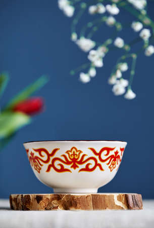 Kazakh traditional tea bowl kese with black tea and milk inside near flowers at blue