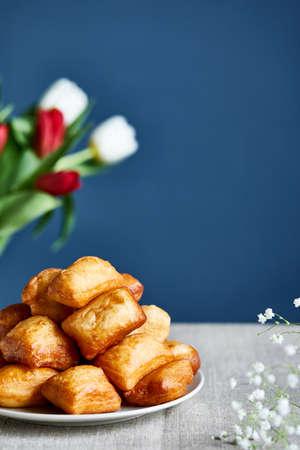 Kazakh national fry bread baursaks and tulips during Nauryz festival on blue