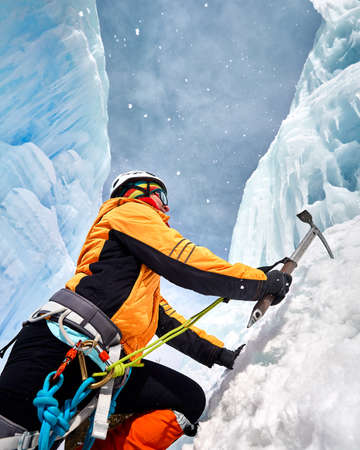 Woman climber in orange jacket with ice axe near frozen waterfall in the mountains Stock Photo