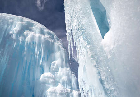 Frozen mountain waterfall with icicles against blue sky and forest at background Stock Photo
