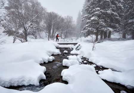 Woman with show shoes is crossing bridge across the river in the winter snowy forest in Almaty, Kazakhstan