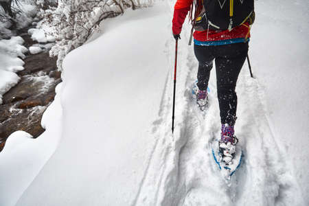 Woman wearing with show shoes is walking in the winter snowy forest near the river in Almaty, Kazakhstan