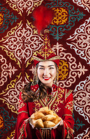 Kazakh woman in red national dress holding plate with baursak bread on oriental ornament background at Nauryz festival Stock Photo