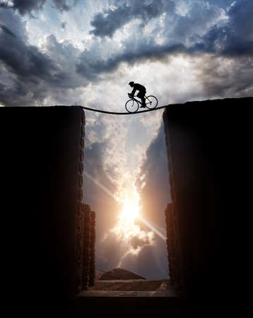 Silhouette of a man on bicycle Cycling over the abyss at sunset cloudy sky background Stock Photo