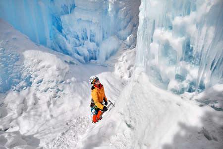 Woman climber in orange jacket with ice axe near frozen waterfall in the mountains in Almaty, Kazakhstan Stockfoto
