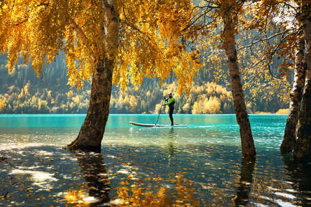 Man floating on a SUP board at mountain lake near yellow forest in autumn time. Adventure at Stand up paddle boarding.