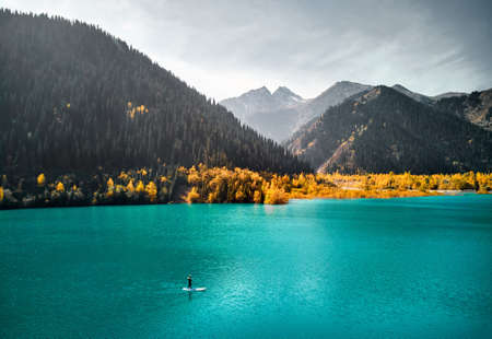 Aerial drone shot of Man floating on a SUP board at mountain lake near yellow forest in autumn time. Adventure at Stand up paddle boarding.