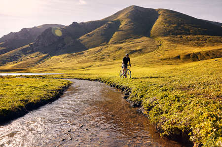 Man on mountain bike rides near the river at the green mountain valley at sunrise. Recreation, travel and healthy lifestyle concept.