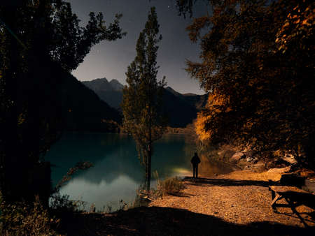 Tourist with headlamp at autumn forest yellow trees against night sky with reflection on Lake Issyk in Kazakhstan