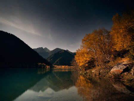 Mountain landscape of autumn forest yellow trees against night sky with reflection on Lake Issyk in Kazakhstan