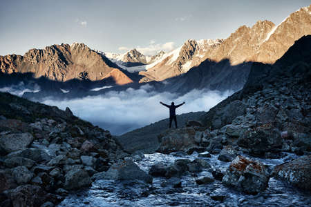 Hiker in silhouette with hands up above the clouds against mountains with snow in Kazakhstan. Outdoor and hiking concept Stock Photo