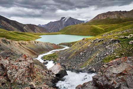 Beautiful Mountain Lake Teshik Kol against cloudy sky in the Terskey Alatay, Kyrgyzstan