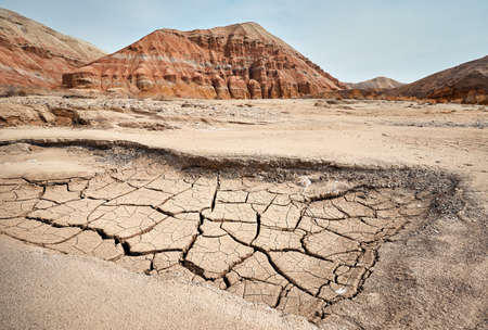 Landscape of Bizarre layered mountain and drought cracked earth in beautiful desert park Stock Photo